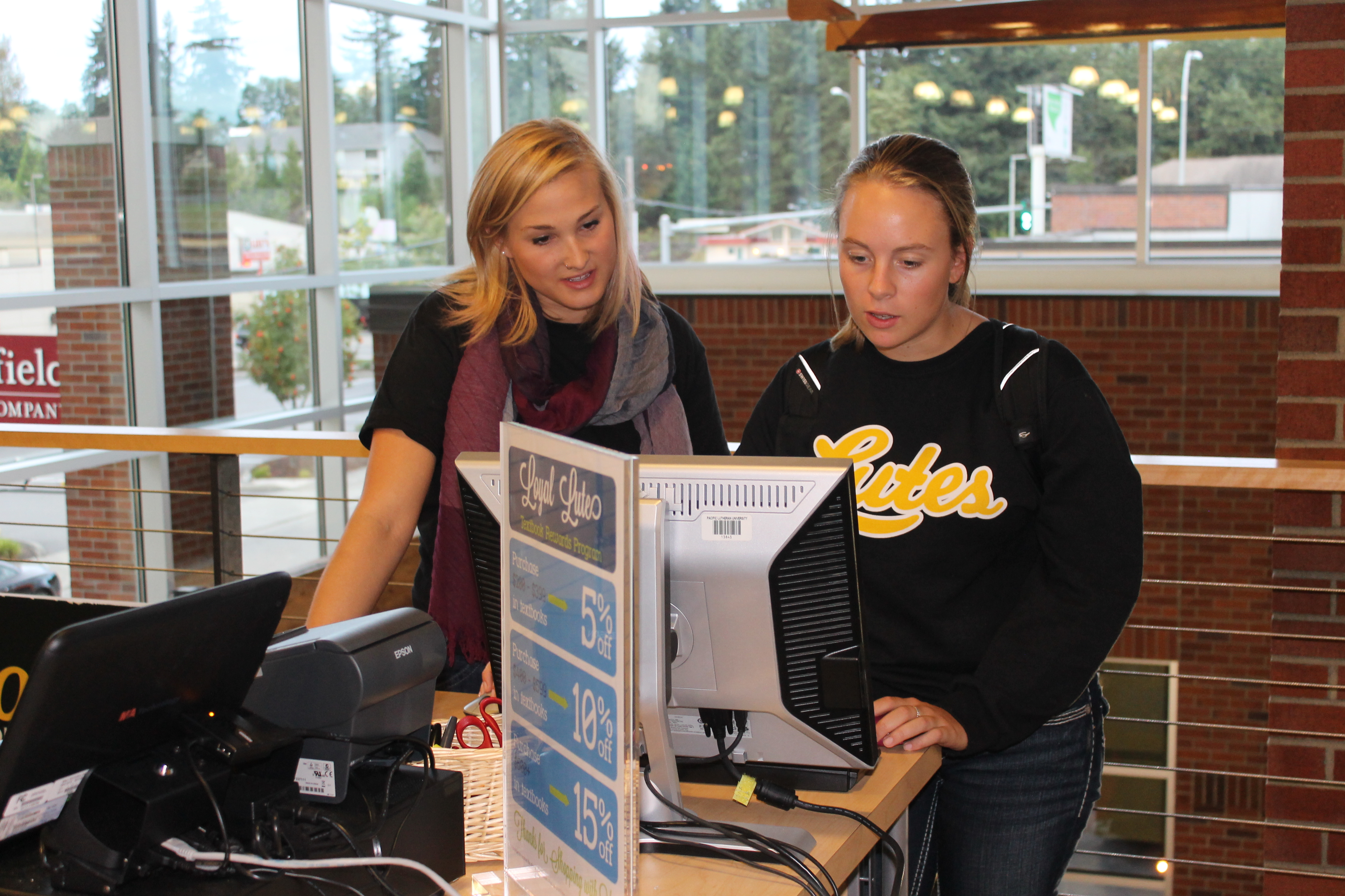 """""""Send a smile specialist"""" Courtney Volta aids fellow sophomore Kelli Breland in looking up her classes at the  textbook counter in the Garfield Book Company."""